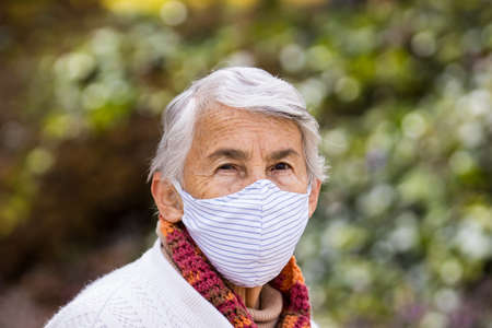 Senior woman wearing a home made face mask and enjoying some time outdoors during the coronavirus quarantine de-escalation