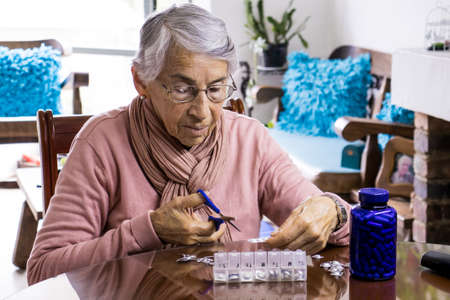 Senior woman at home arranging her prescription drugs into  weekly pill organizer