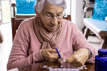 Senior woman at home arranging her prescription drugs into a weekly pill organizer