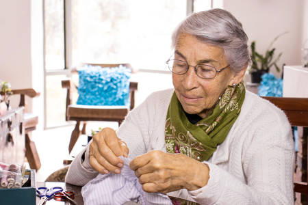 Senior woman sewing a homemade face mask during the Covid-19 pandemic