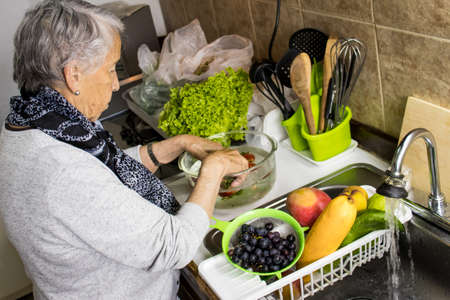 Senior woman disinfecting fruits and vegetables purchased during the COVID-19 pandemic