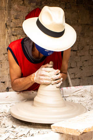 Man making ceramic articles on the potters wheel in a traditional factory in the city of Ráquira located in the department of Cundinamarca in Colombia Stock fotó