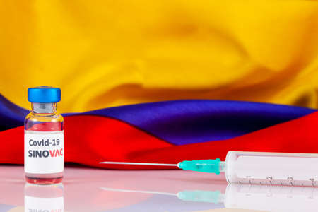 BOGOTA, COLOMBIA - FEBRUARY 2021. Sinovac covid vaccine vial and Colombian flag. Vaccination concept. Sajtókép