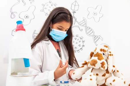 Young girl vaccinating. Young girl playing a life sciences professional role. Could be biologist, doctor, researcher, veterinary. Dreaming about the future.