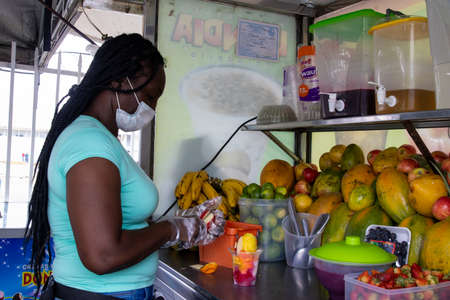 CALI, COLOMBIA - SEPTEMBER, 2021: Woman at the city of Cali in Colombia preparing and selling a traditional sweet water ice with fruits called cholado