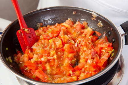 Preparation of the traditional Colombian hogao or criollo sauce (salsa criolla) made of onion, tomato, peppers and cilantro Standard-Bild