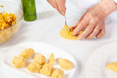 Preparation of the traditional patties from the region of Cauca in Colombia, called empanadas de pipián - Senior woman filling the patties Standard-Bild