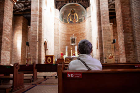 Senior woman praying at the historical Cathedral of Our Lady of Poverty of Pereira, built in 1890 Standard-Bild