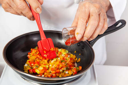 Preparation of the traditional patties from the region of Cauca in Colombia, called empanadas de pipián - Senior woman preparing the filling for the patties - Adding spicy sauce Standard-Bild
