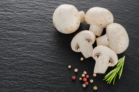 black board: Fresh mushrooms with spices and herbs on a black board.