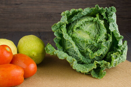 Assortment of fresh cabbages, tomatoes and lemons on brown background photo