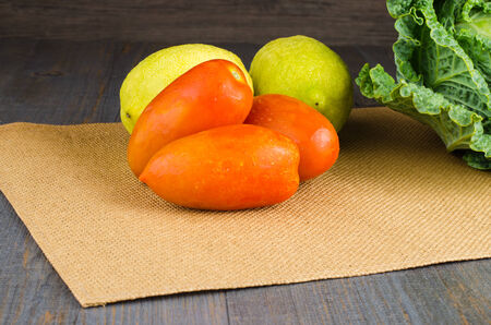 Assortment of fresh tomatoes, lemons and cabbages on brown background photo