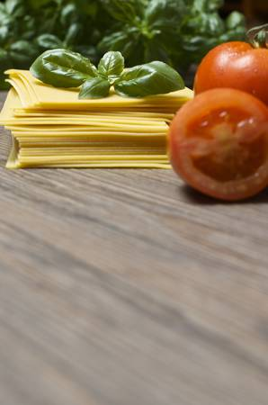 Raw pasta lasagna with basil leaves and fresh tomatoes on wooden background