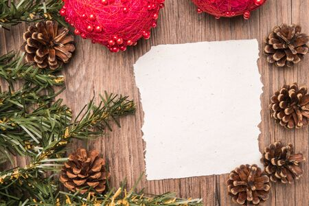 oak: Christmas border design with pine cone, fir branches and christmas balls on parchment paper over old oak wood