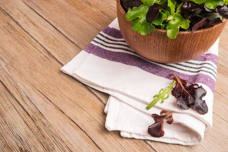 romaine: Fresh green salad with spinach, arugula, romaine and lettuce in a bowl on rustic wooden background