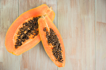 Sliced fresh papaya on wooden background. Top view with copy space Reklamní fotografie