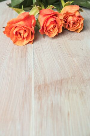 rosas naranjas: A bouquet of orange roses on wooden table. Copy space