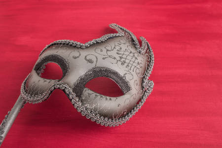 facemask: Colorful carnival mask on a red textured background. Masks with theater concept. Top view with copy space Stock Photo