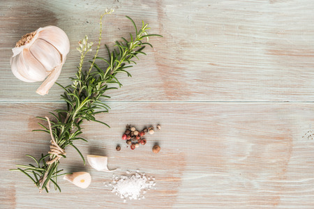 copy space: Bunch of fresh of garden rosemary on wooden table, rustic style, fresh organic herbs with salt, chili and garlic. Stock Photo