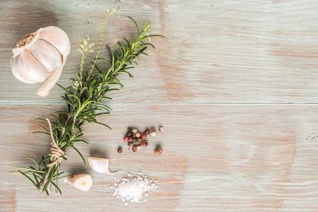 ajo: Manojo de romero fresco del jardín en la mesa de madera, estilo rústico, hierbas orgánicas frescas con sal, chile y ajo.