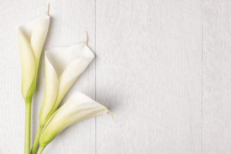 エレガントな春の花、素朴な木製のテーブルのオランダカイウユリ。結婚式の背景画像。