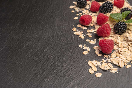 Healthy breakfast. Fresh granola, oatmeal with blackberries and raspberries on a black slate background. copy space