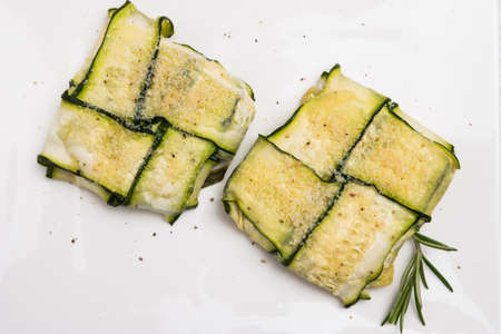 courgettes: Oven baked courgettes stuffed with cheese, garlic and herbs. Courgette recipe in the oven. Top view with copy space.
