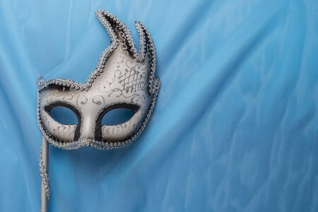facemask: Colorful carnival mask on wavy blue satin fabric background.