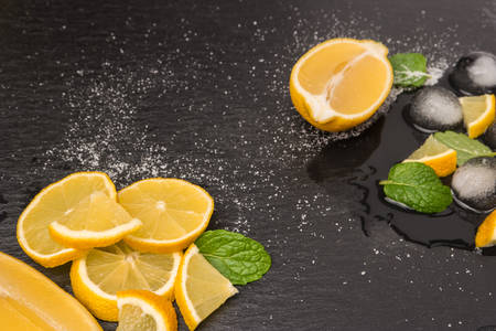 Slices and half fresh juicy lemon with mint leaves and melting ice on a slate board