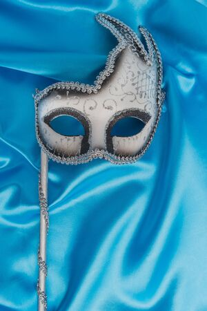 Colorful carnival mask on wavy blue satin fabric background. Top view with copy space. Stock Photo