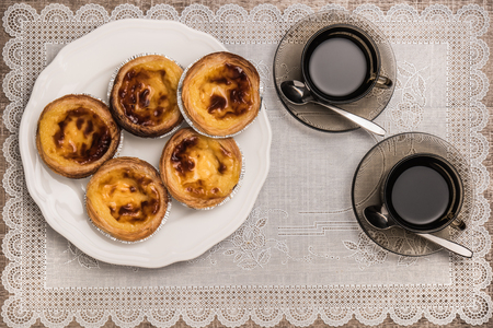 Pastel de nata, typische Portugese ei taart gebak en zwarte koffie op een gedekte tafel. Bovenaanzicht met een kopie ruimte