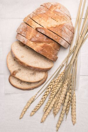 Fresh homemade bread and wheat spike on wooden background. Top view with copy space. Stock Photo