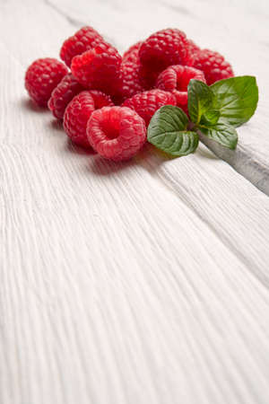 Ripe sweet raspberries on wood table background