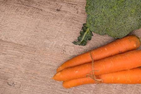 grocer: Fresh vegetables from the garden, carrots and broccoli on a wooden table. Vegetables for preparing soup