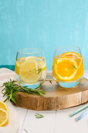 Detox fruit infused flavored water. Refreshing summer homemade cocktail with orange, lemon and rosemary leaves