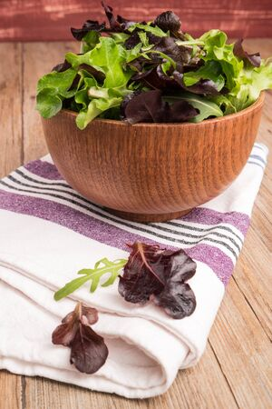 Fresh green salad with spinach, arugula, romaine and lettuce in a bowl on rustic wooden background