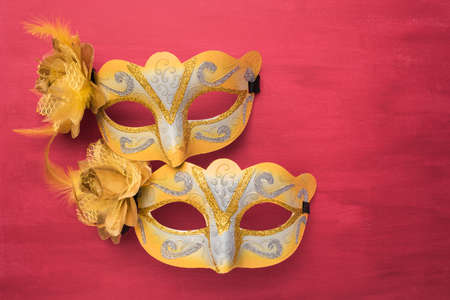 canvass: Colorful carnival mask on a red textured background. Masks with theater concept. Top view with copy space Stock Photo