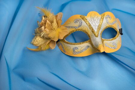 canvass: Colorful carnival mask on wavy blue satin fabric background.