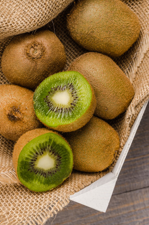 Box of fresh kiwi in on wooden background. Top view with copy space