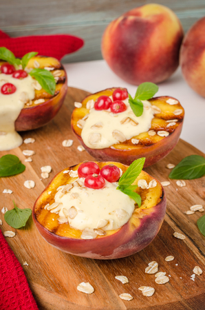Grilled peaches with yogurt, gooseberries and mint leaves on wooden table Stock Photo