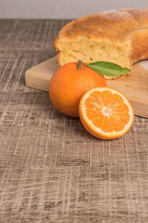 Slices of clementine cake with powdered sugar topping. Cake on a board with fresh clementines on wooden board. Stock Photo