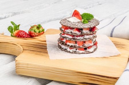 Chocolate belgian waffles with strawberries, whipped cream and mint leaf on wooden table
