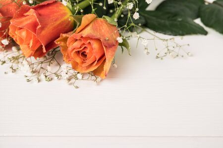A bouquet of orange roses and gypsophila on wooden table. Copy space Stock Photo