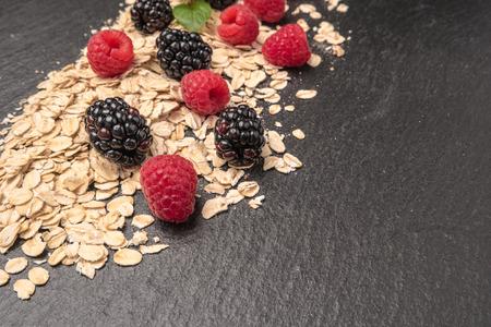 Healthy breakfast. Fresh granola, oatmeal with blackberries and raspberries on a black slate background. copy space