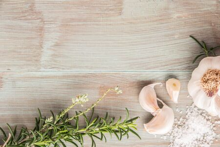 Bunch of fresh of garden rosemary on wooden table, rustic style, fresh organic herbs with salt and garlic. Top view with copy space Stock Photo