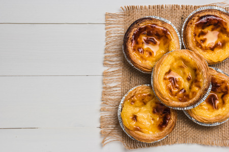 Pasteis de nata, typical Portuguese egg tart pastries on a set table. Top view with copy space
