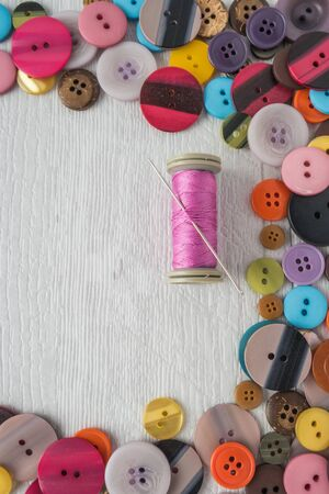 Sewing needle threaded with a orange thread ready for sewing. Buttons frame. Scene on a rustic wooden table. Top view with copy space.