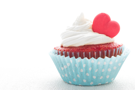 Red velvet heart cupcake with cream cheese frosting and a red heart for Valentines Day. White background with copy space Stock Photo