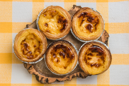 belem: Pasteis de nata, typical Portuguese egg tart pastries on a set table. Top view with copy space