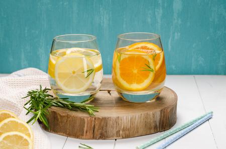 Detox-Frucht mit aromatisiertem Wasser. Erfrischendes selbst gemachtes Sommercocktail mit Orangen-, Zitronen- und Rosmarinblättern